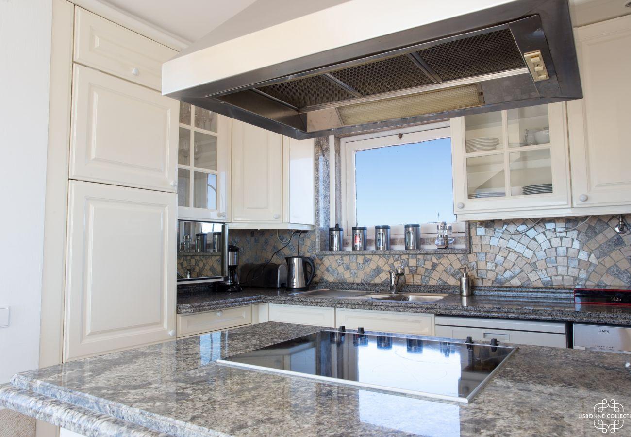Cozinha espaçosa e luminosa com bancada de mármore na cobertura