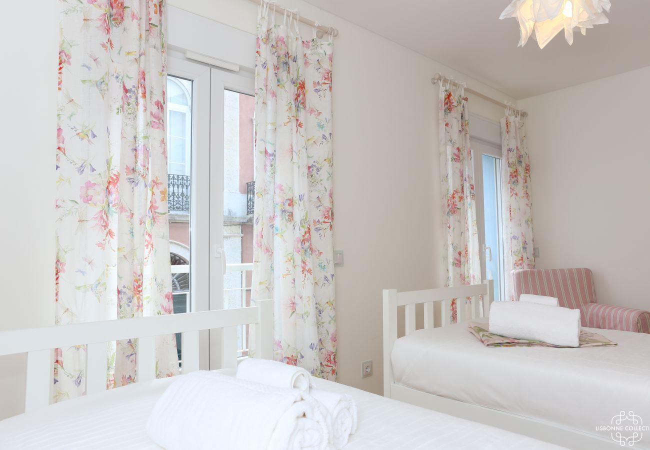Quarto Deluxe com duas camas de solteiro, um sofá individual e acesso à varanda