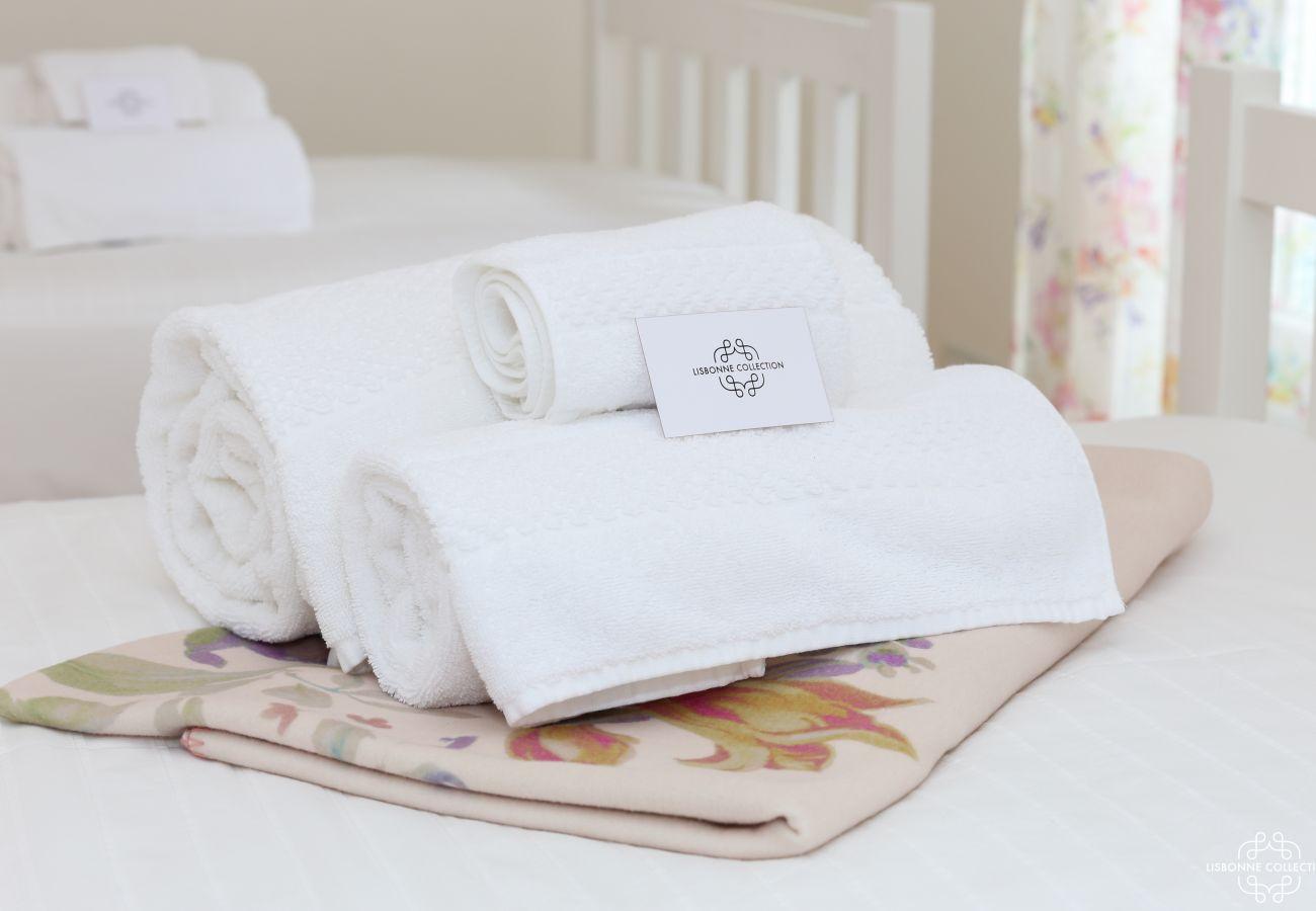 Toalha de banho dobrada e colocada na cama com a caixa