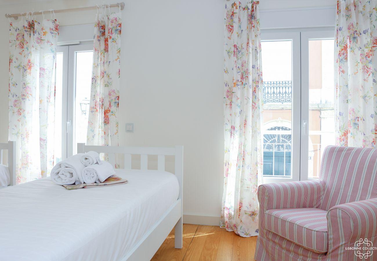 Quarto luminoso com duas camas de solteiro, um sofá único e acesso à varanda