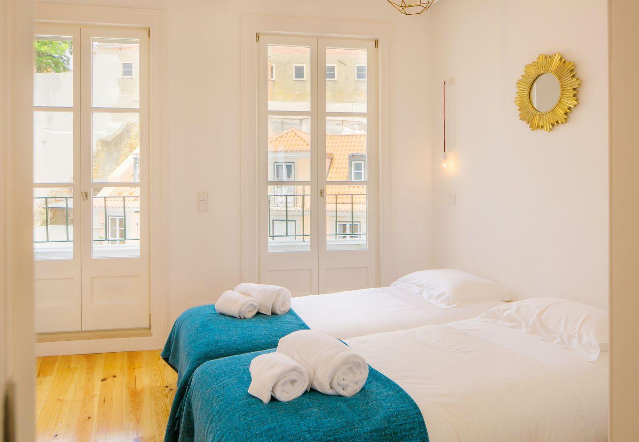 quarto com duas camas individuais contemporâneas com vista para o centro da cidade de Lisboa