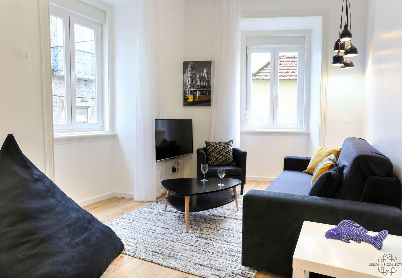 sala de estar com duas janelas que abrem no bairro da Graça
