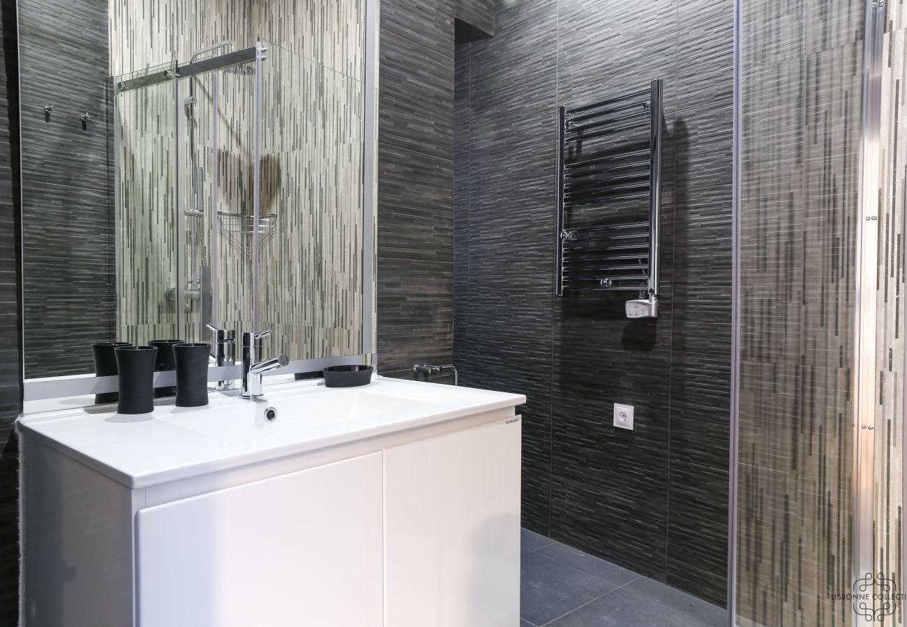 chuveiro espaçoso e moderno com lavatório, vaso sanitário e radiador e aquecedor de toalhas