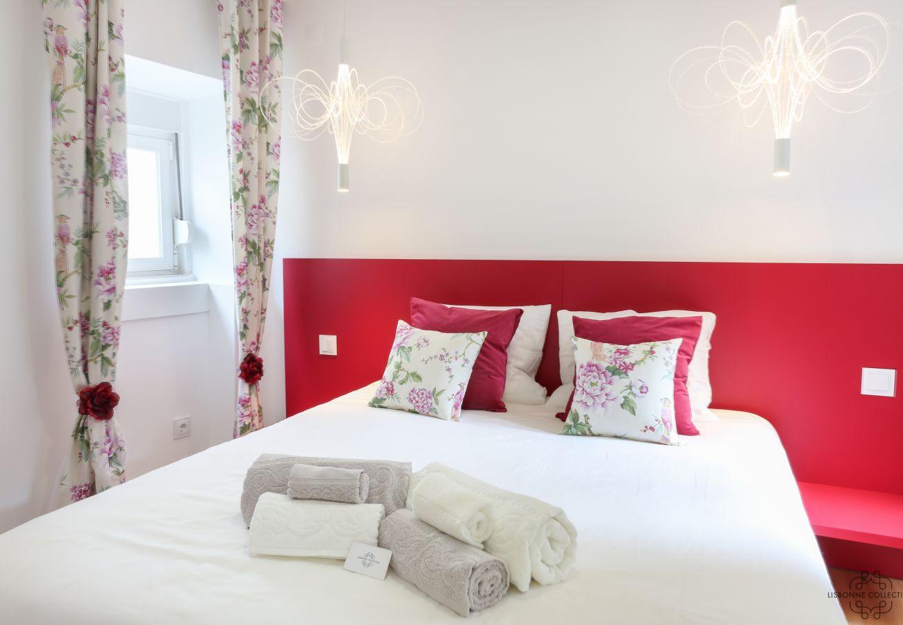 quarto principal colorido e despojado com toalhas dobradas na cama