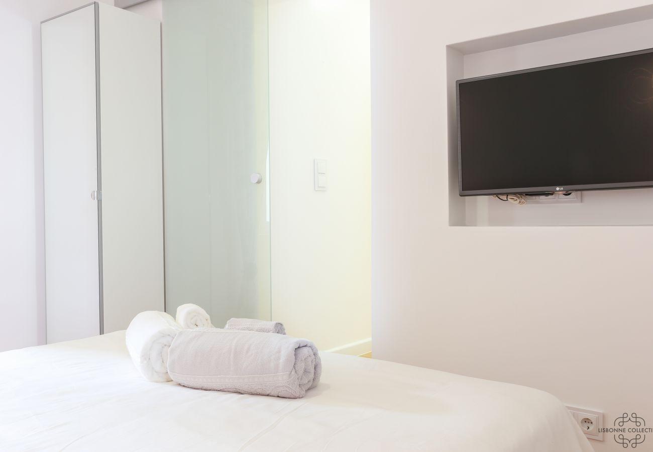sala acolhedora e brilhante com TV embutida na parede em frente da cama