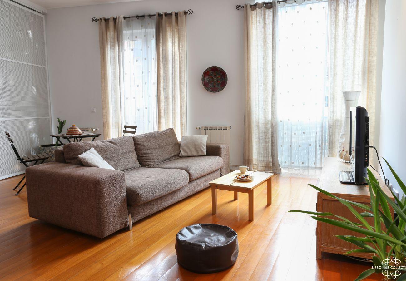 Espaçosa sala de estar comunicando-se em um quarto e uma cozinha americana