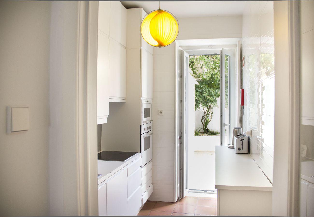 cozinha brilhante de Lisboa que se abre para um pátio interior acolhedor e florido