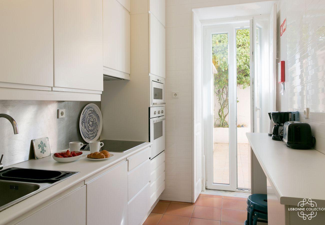 cozinha de alto padrão com forno, microondas, fogão elétrico que abre para um pátio interior acolhedor e florido