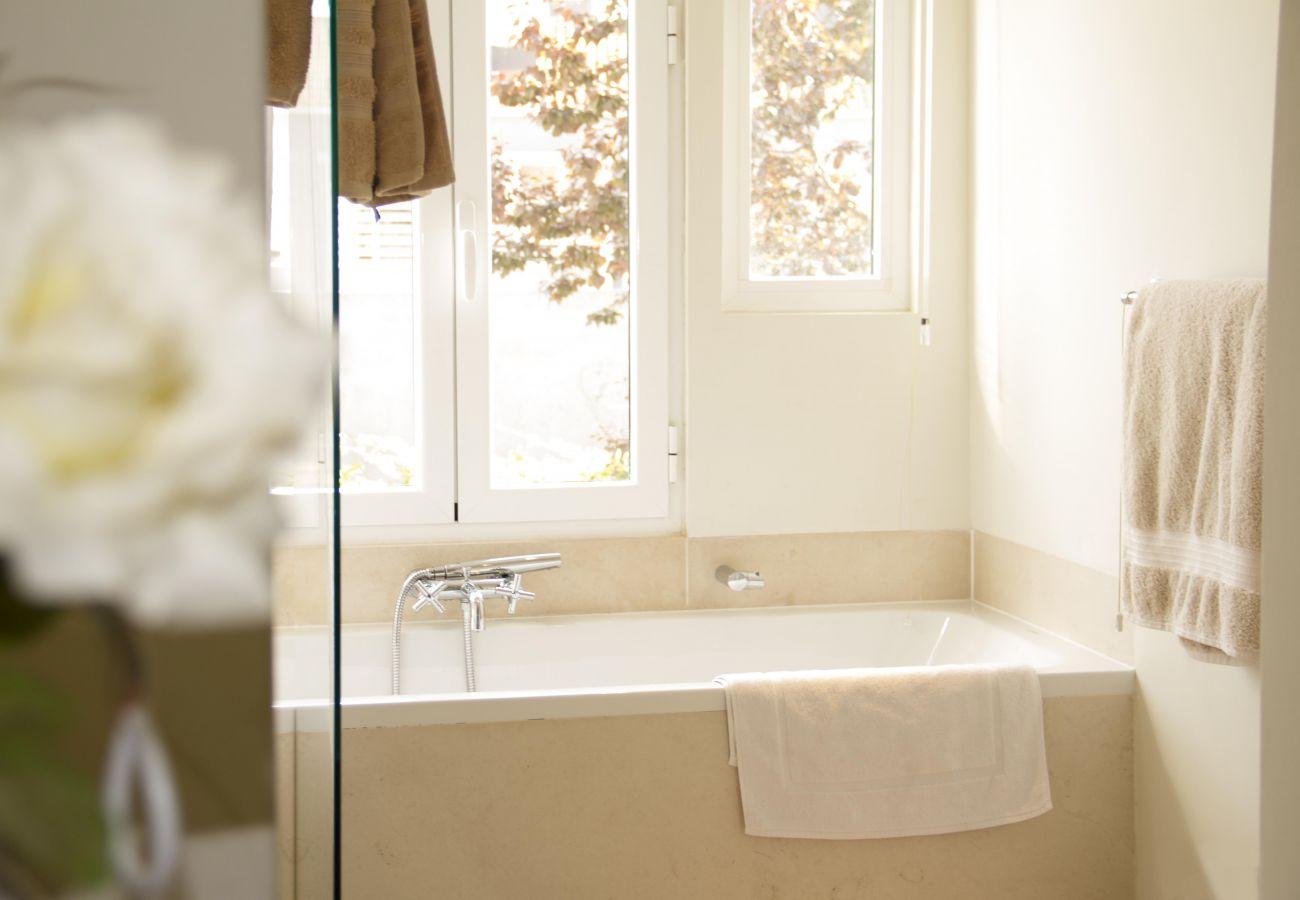 banheiro com banheira em tons puros com vista para o pátio interior