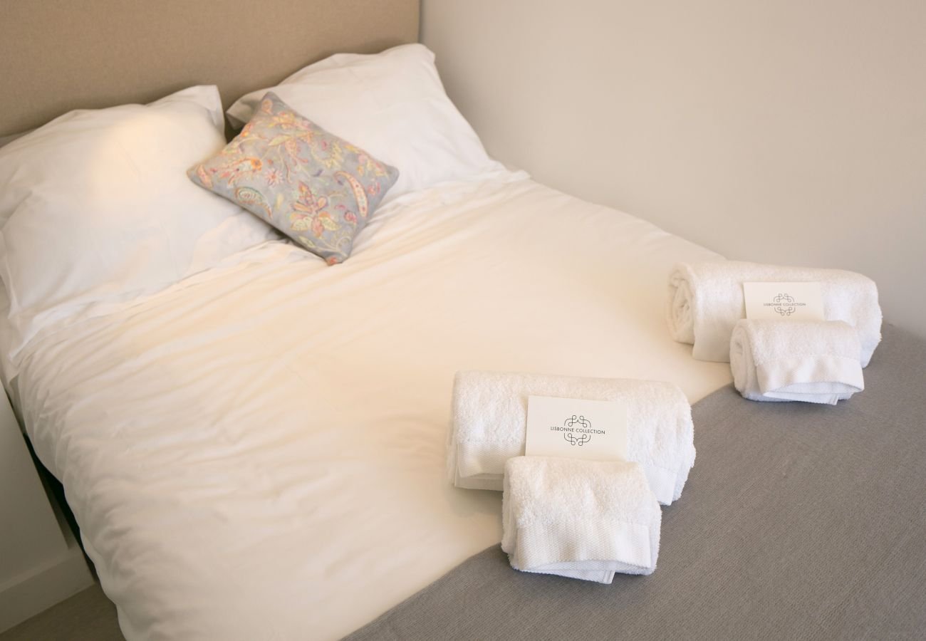 Cama de casal com toalhas dobradas na cama no centro histórico de Lisboa