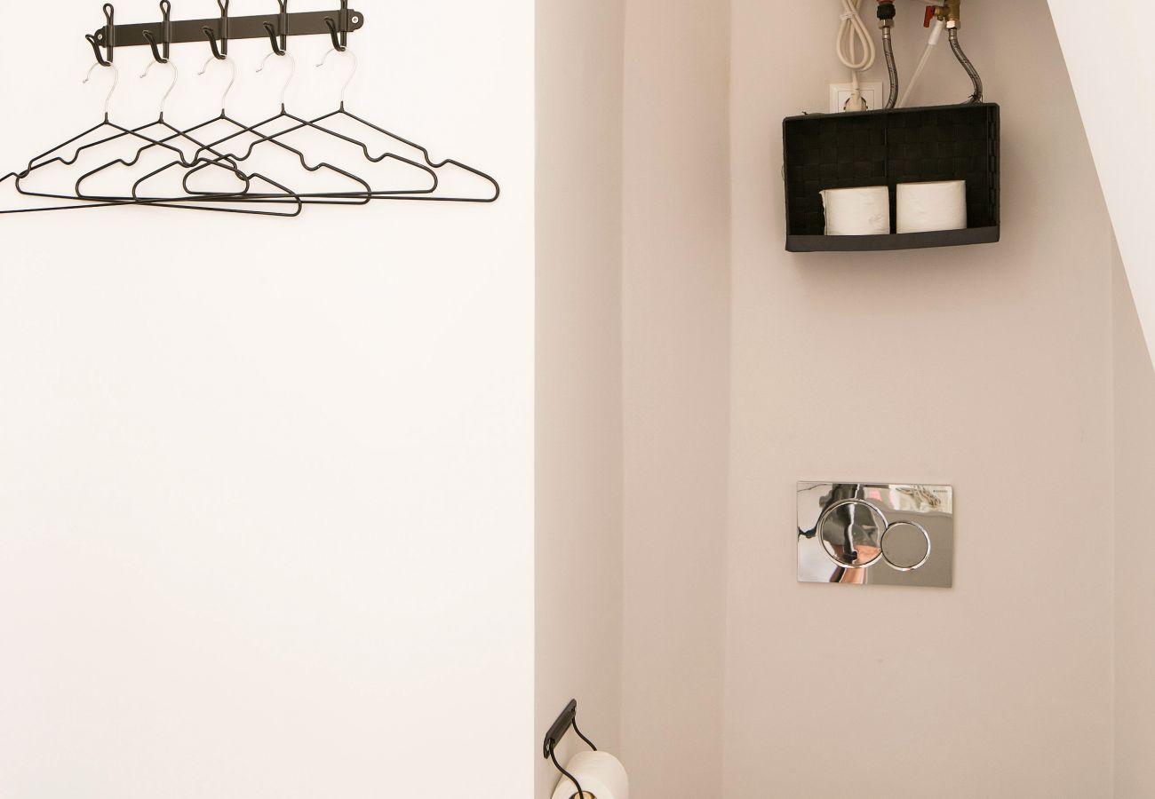 Guarda-roupa com cabide e decoração nas paredes em cores claras