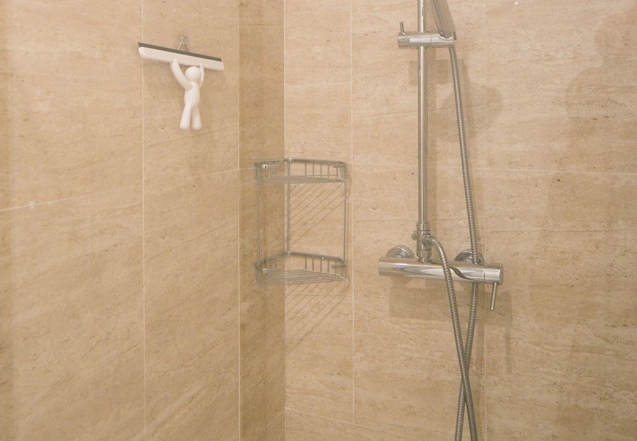 Chuveiro espaçoso e moderno com lavatório, vaso sanitário e toalheiro