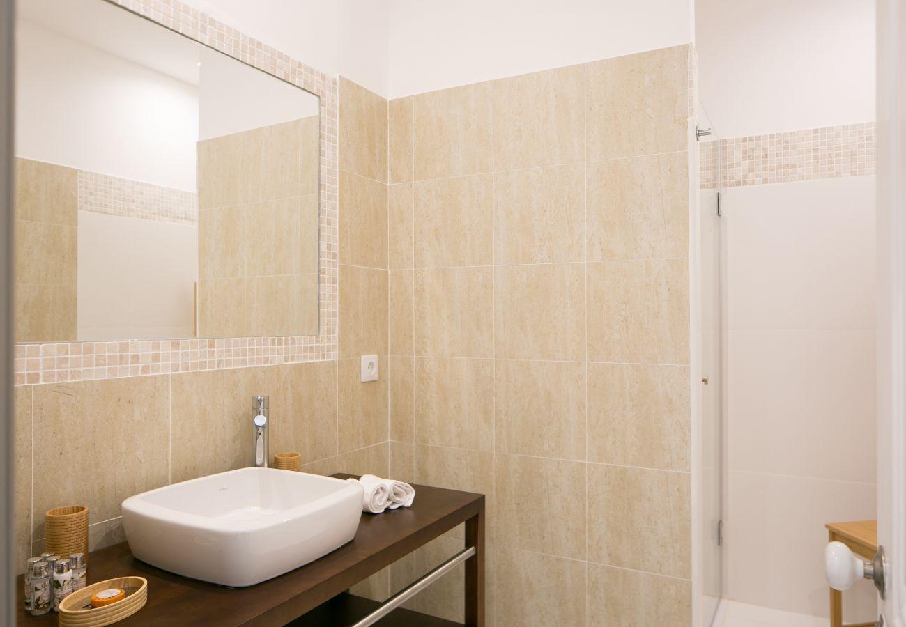 Casa de banho com móveis de madeira de vaidade e chuveiro