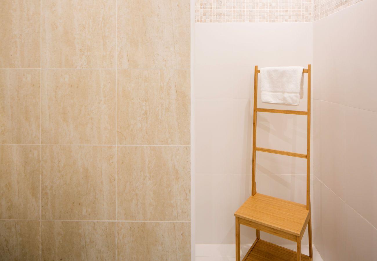 Secador de toalha na frente de um chuveiro no banheiro