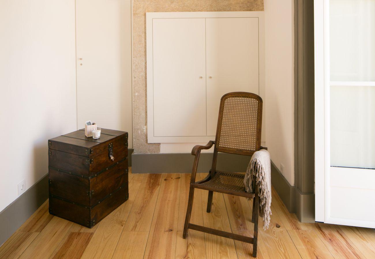 Decoração com cadeira rústica e mesa de cabeceira de madeira na frente de uma janela