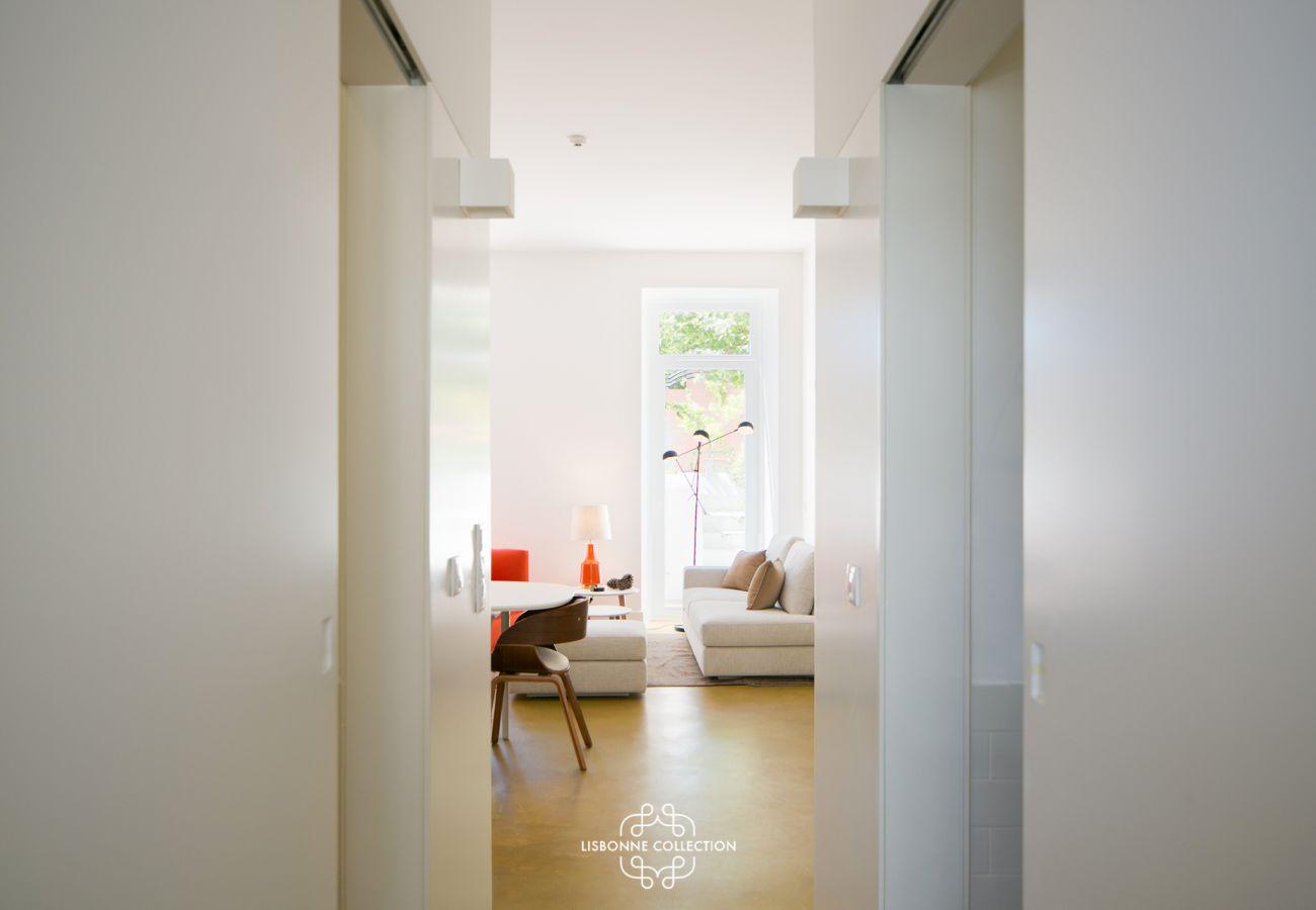 Corredor que leva a uma sala de estar com terraço ao fundo
