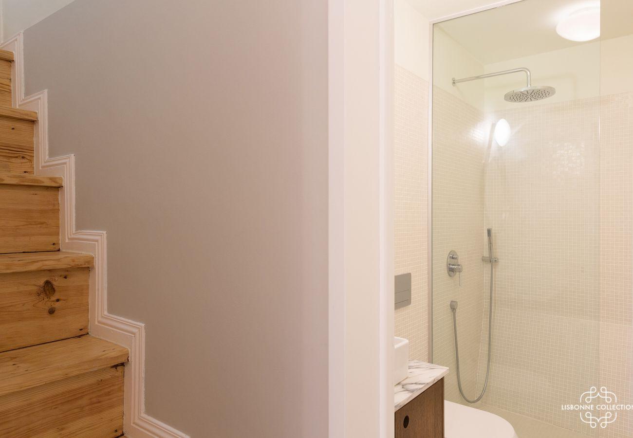 Apartamento duplex com banheiro com chuveiro, vaso sanitário e pia