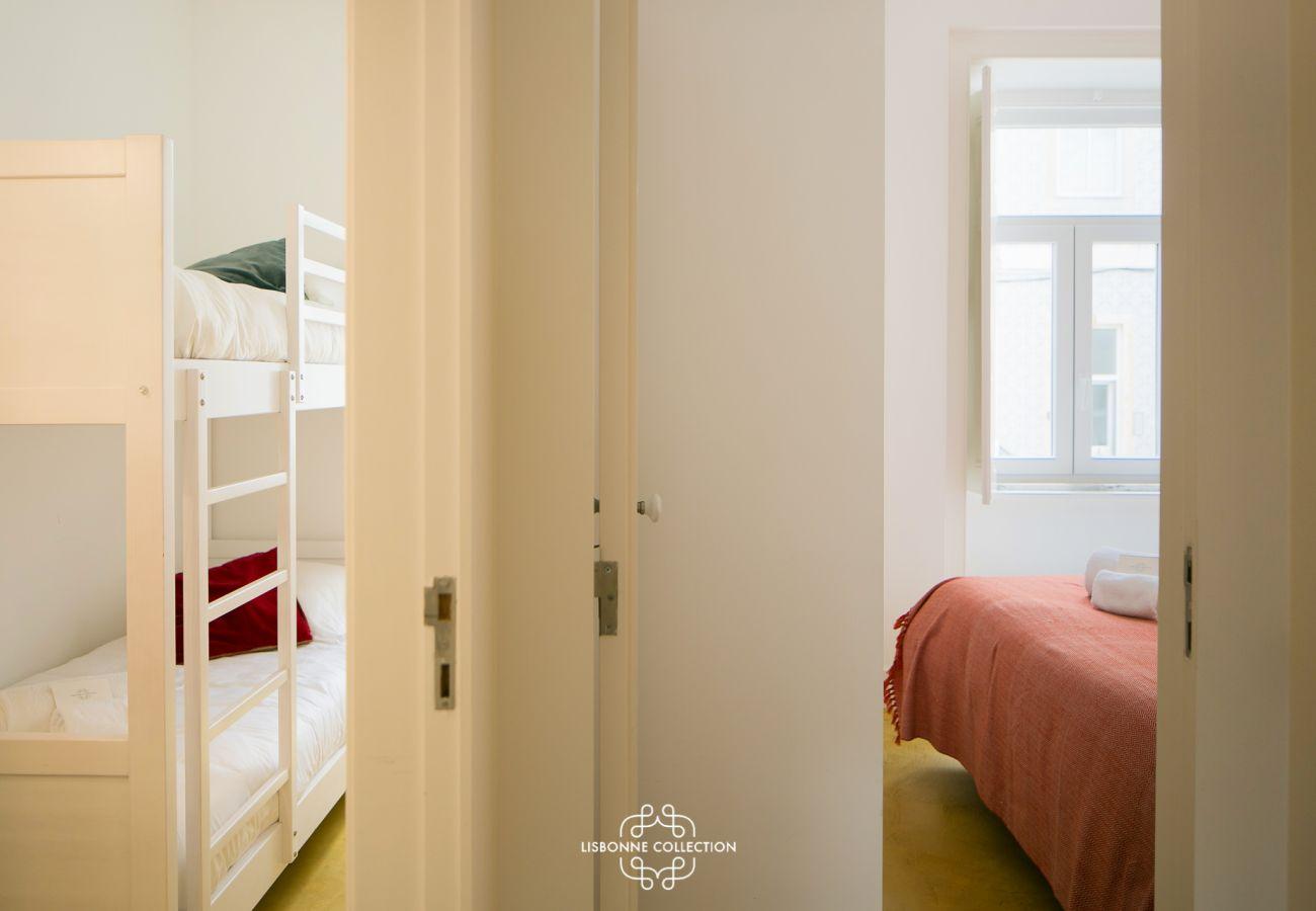 Um quarto duplo para adultos e um quarto de crianças com cama alta