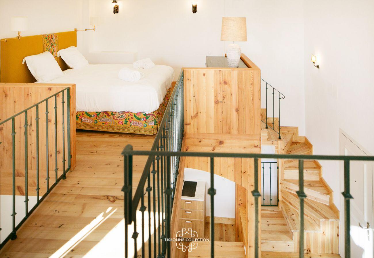 Sala de estar e cozinha com um mezanino que dá acesso ao quarto