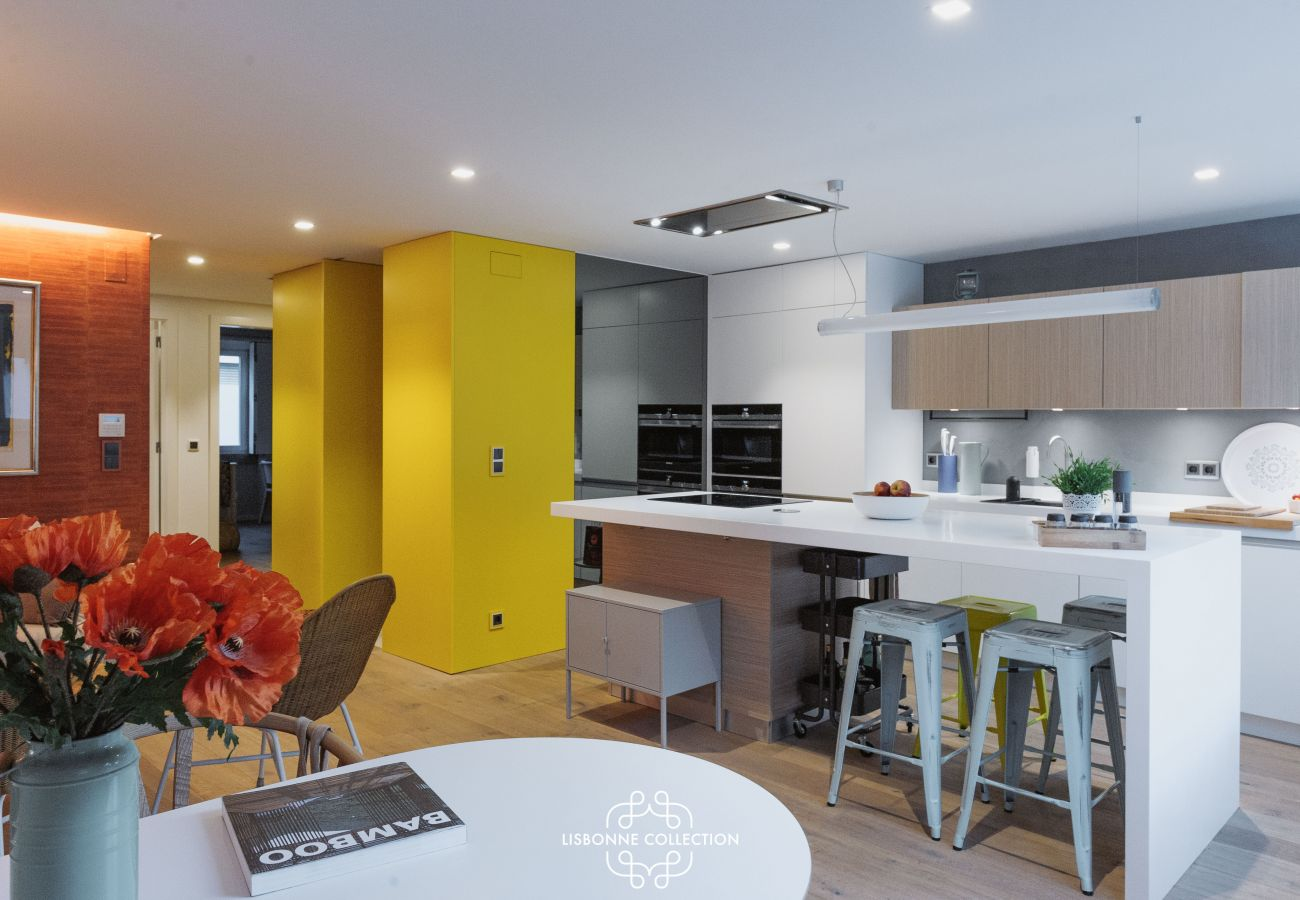 Grande cozinha com fogão ilha central, geladeira e pia