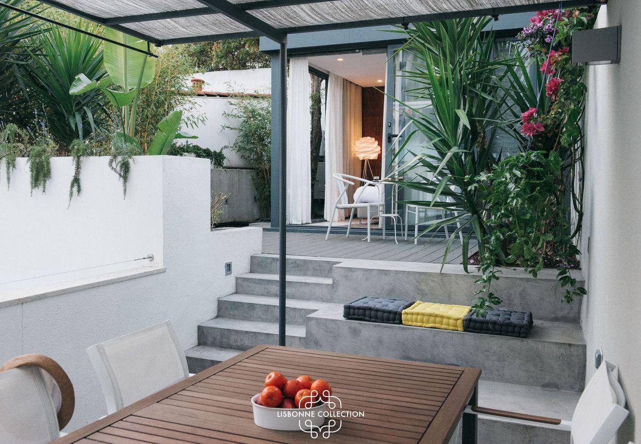 Esplanada ajardinada com plantas e grandes janelas de sacada