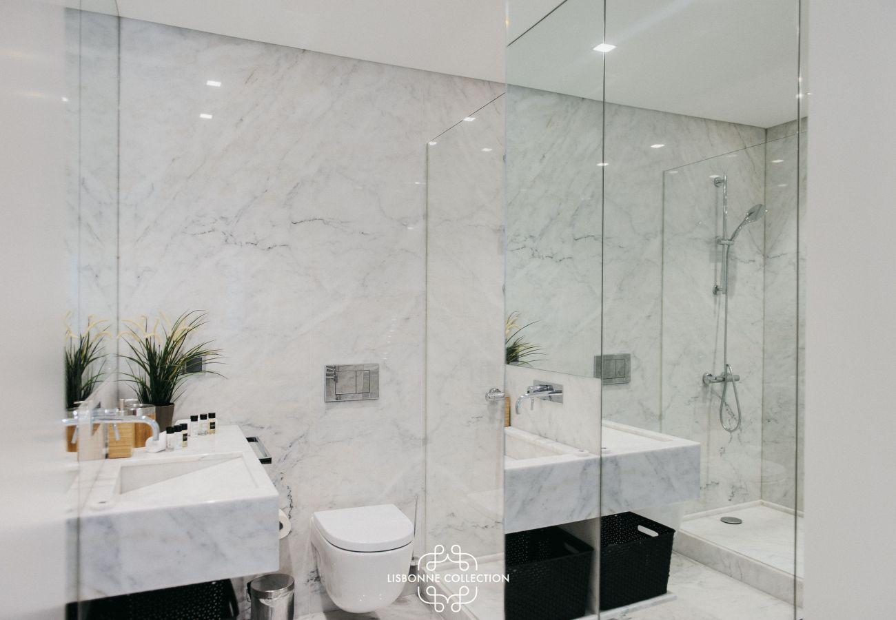 Luxuosa casa de banho em mármore com chuveiro, sanita e lavatório