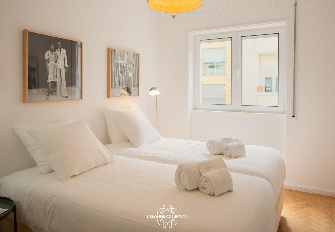 Grande sala de designer com duas camas de solteiro para alugar