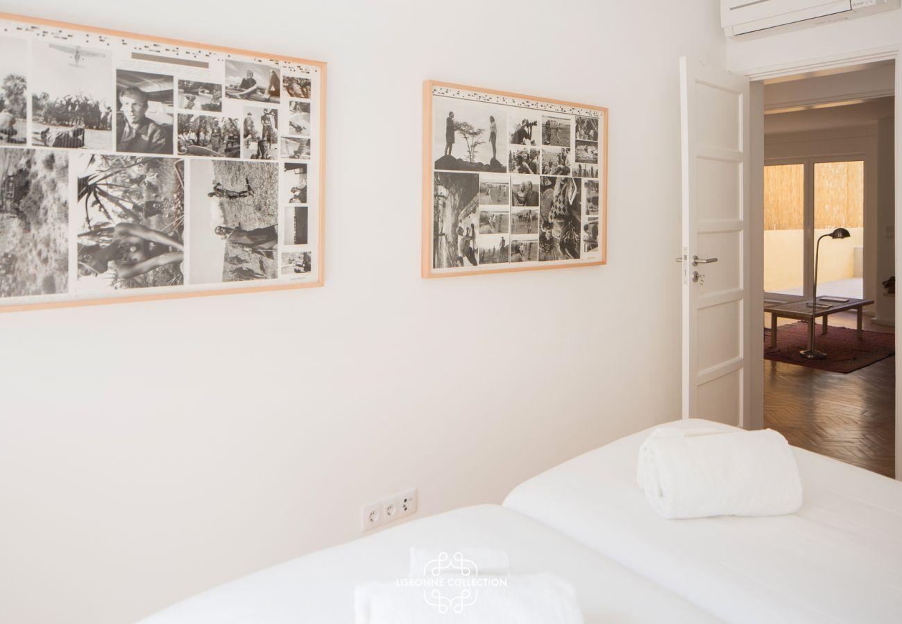 Quarto com duas camas de solteiro com fotos históricas nas paredes