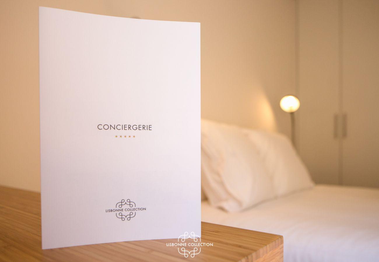 Placa de serviço de concierge na mesa de cabeceira perto da cama de casal