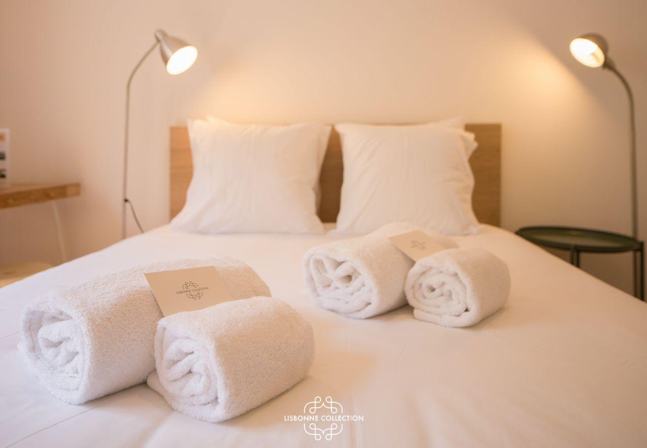 Cama de casal com toalhas dobradas em cima pronto para uso