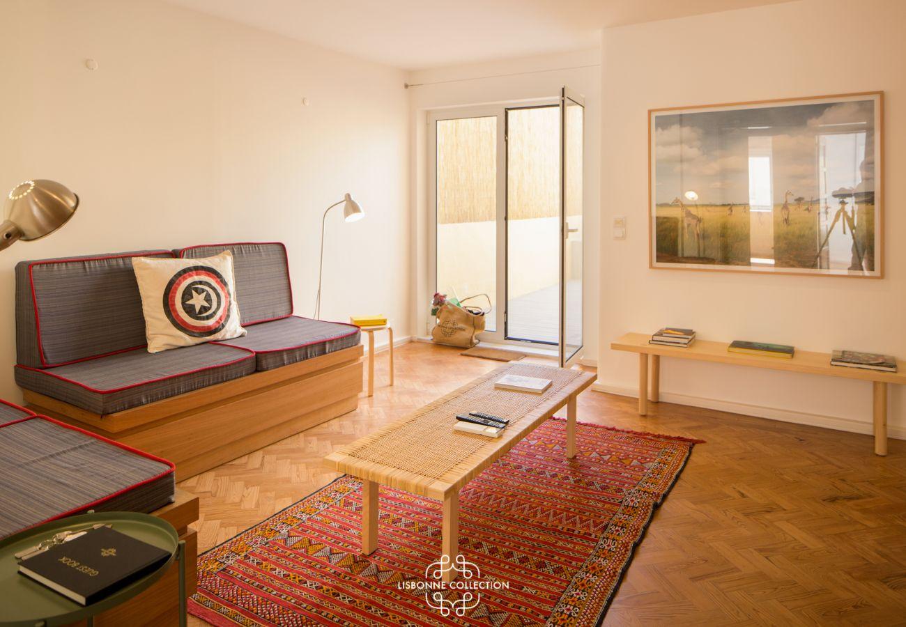 Sala de estar com sofá, acesso à cozinha e terraço com cores vibrantes