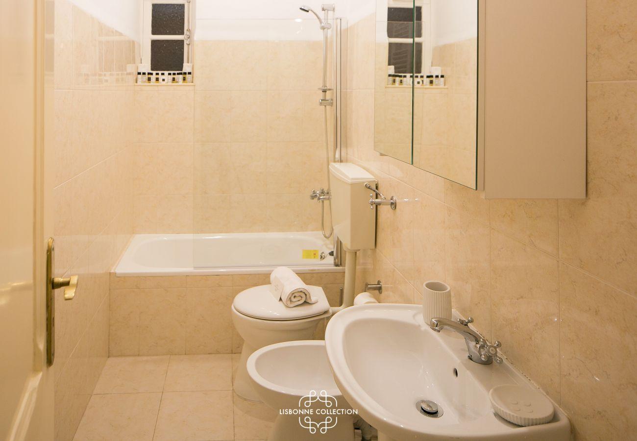 casa de banho bege com banheira grande, bidé e lavatório