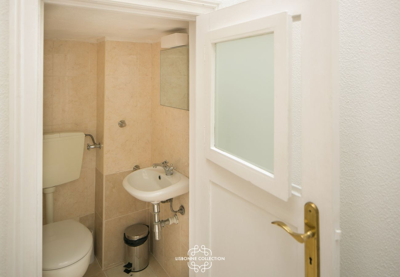 pequeno banheiro típico com porta de madeira