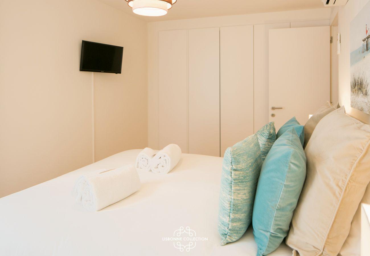 Almofadas azuis empilhadas na cama com lençóis brancos
