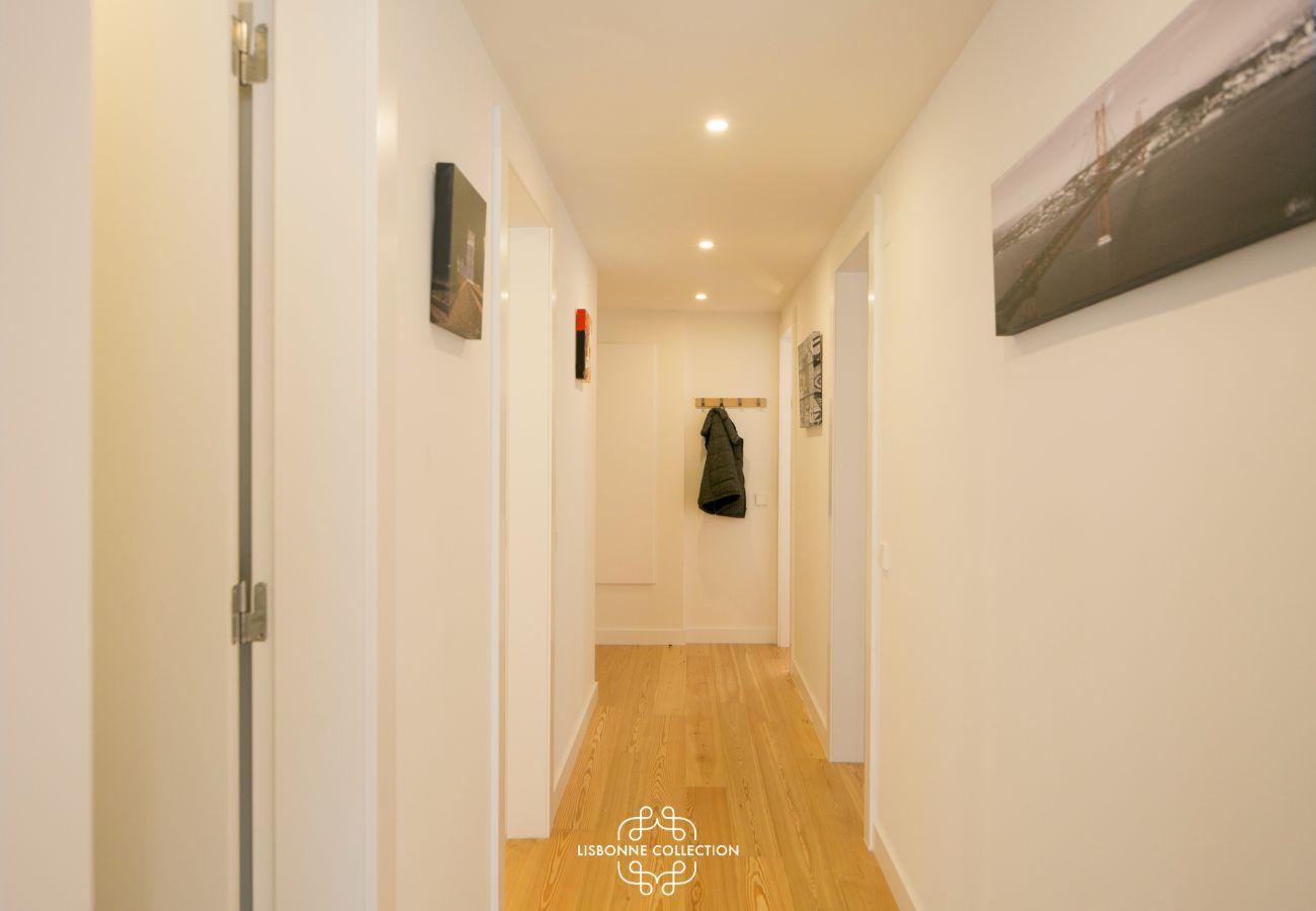 grande corredor com paredes brancas e portas e piso de madeira
