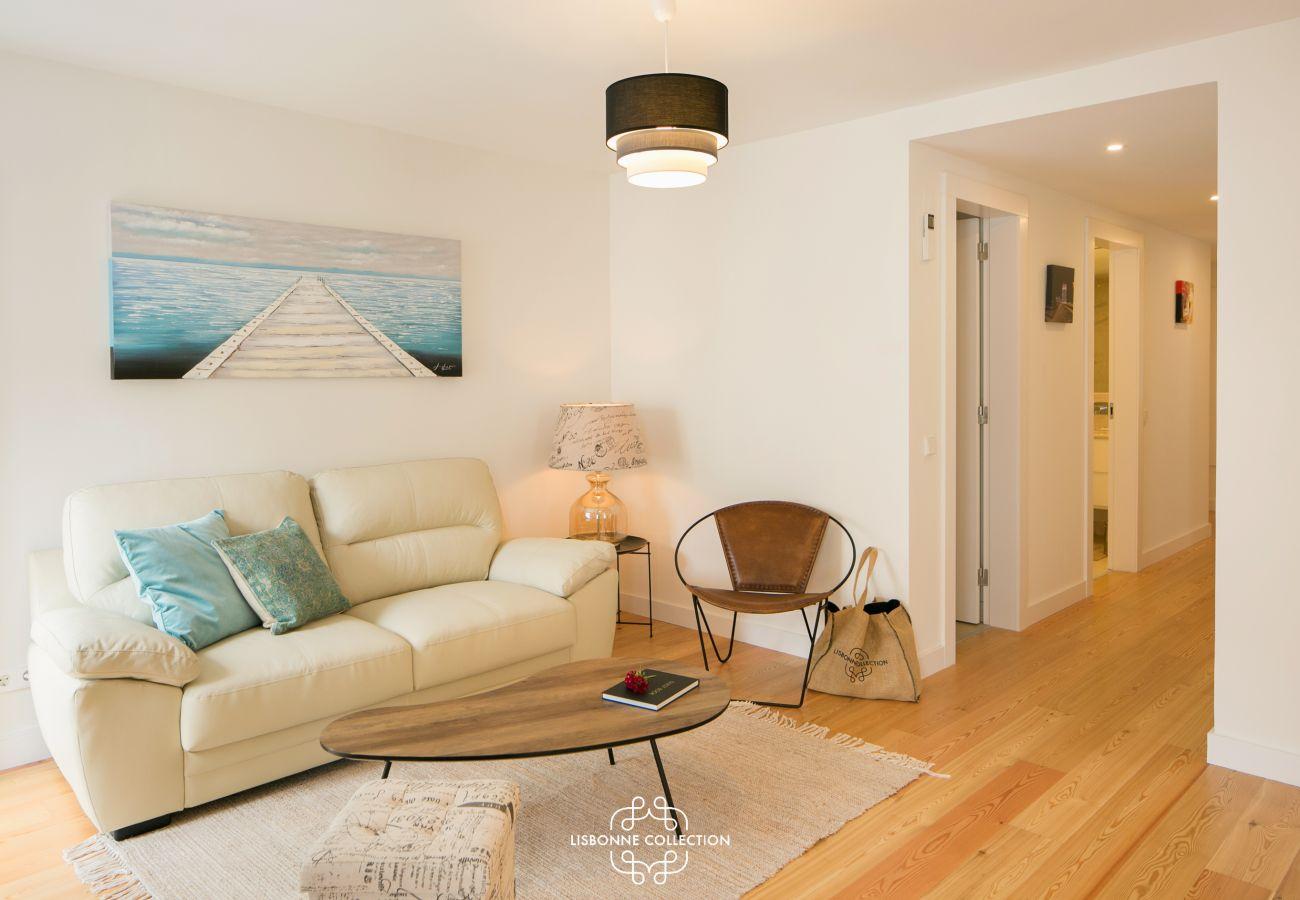 Sala de estar equipada com um sofá com acesso ao corredor da entrada do apartamento