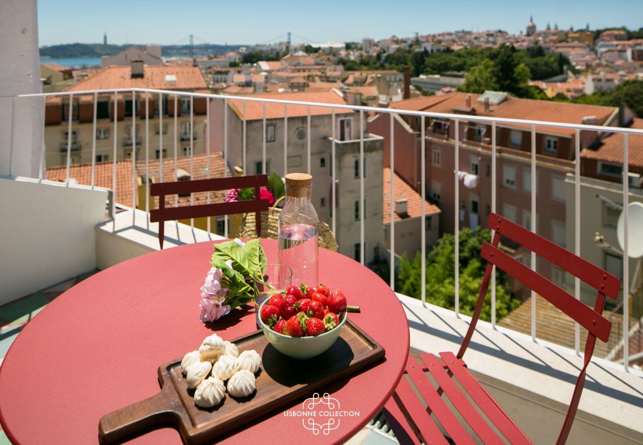 terraço mobilado com mobiliário vermelho e amplo panorama de Lisboa
