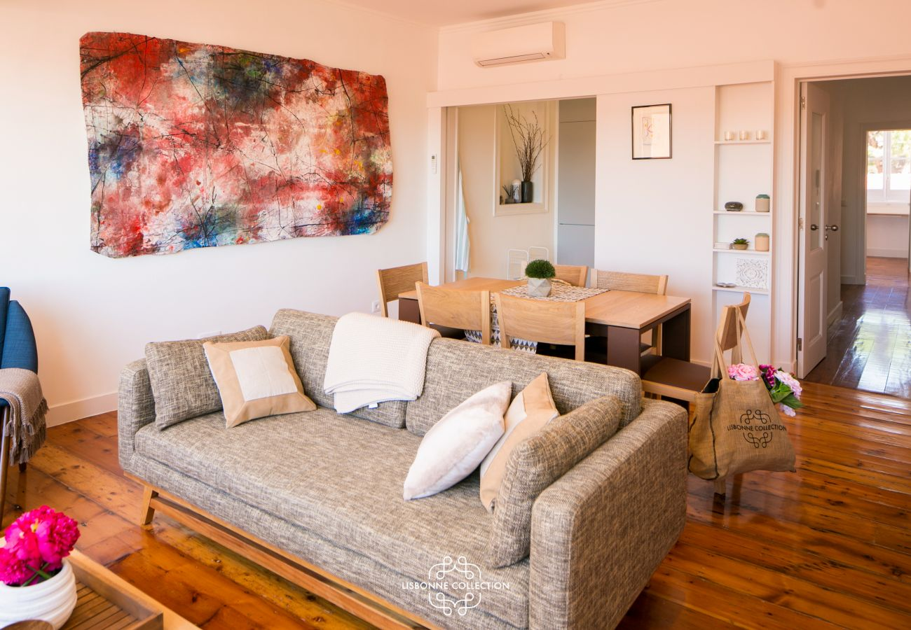sofá na sala ao lado de uma tela de arte abstrata